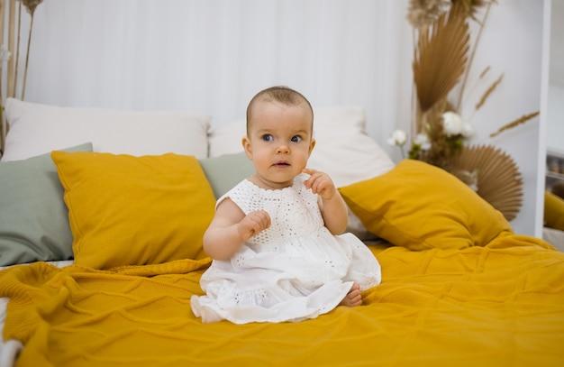 Klein meisje in een witte jurk zit op een gele deken op een bed met ruimte voor tekst
