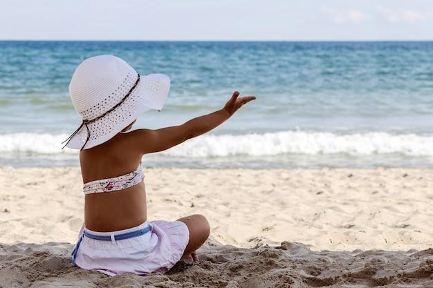 Klein meisje in een witte strandhoed en bikini zit op het zand aan zee met haar rug naar de camera