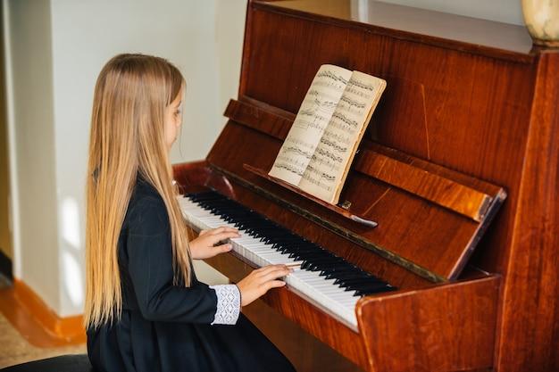 Klein meisje in een zwarte jurk leert piano spelen. het kind speelt een muziekinstrument.