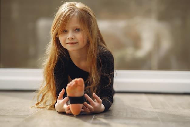 Klein meisje in een zwarte sportkleding houdt zich bezig met gymnastiek