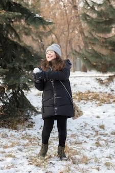 Klein meisje in een zwarte winterjas en grijze gebreide muts speelt sneeuwballen in het bos