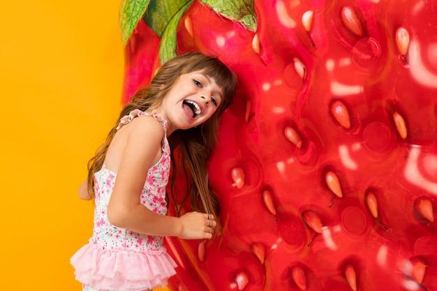 Klein meisje in een zwembroek met een luchtbed in de vorm van aardbeien op een oranje muur