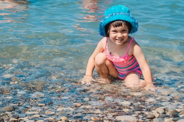 Klein meisje in een zwempak die haar benen in het overzees bespat