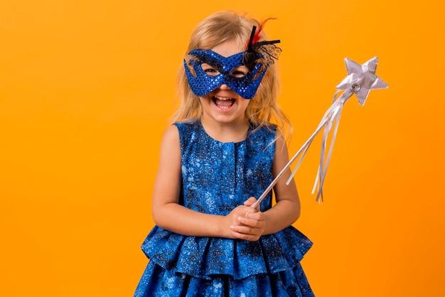 Klein meisje in fee kostuum met masker en toverstaf