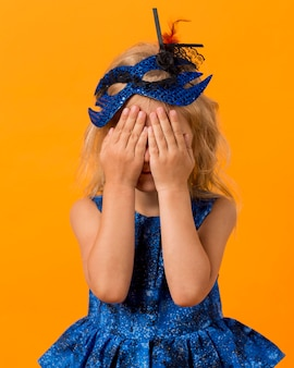 Klein meisje in fee kostuum met masker