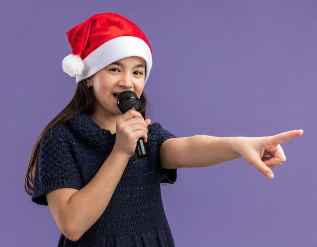 Klein meisje in gebreide jurk dragen kerstmuts bedrijf microfoon spreken met wijsvinger naar iets gelukkig en vrolijk permanent over paarse achtergrond