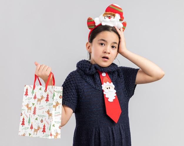 Klein meisje in gebreide jurk dragen rode stropdas met grappige kerstrand op hoofd met papieren zak met kerstcadeau op zoek verward met hand op haar hoofd