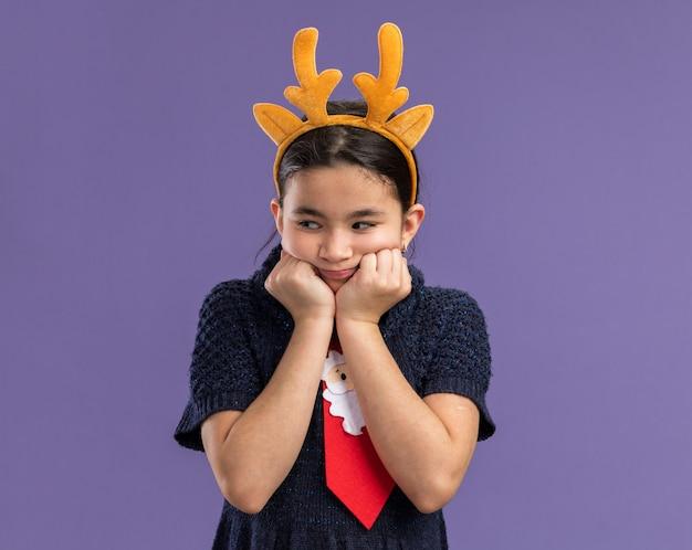 Klein meisje in gebreide jurk dragen rode stropdas met grappige rand met herten hoorns op hoofd opzij kijken bezorgd staande over paarse achtergrond