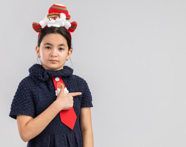 Klein meisje in gebreide jurk, gekleed in een rode stropdas met grappige kerstrand op het hoofd en kijkt met een ernstig gezicht dat met een uit-vinger naar de zijkant wijst