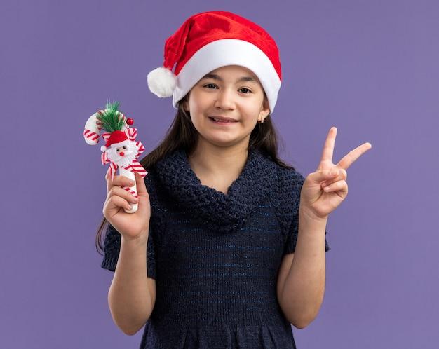 Klein meisje in gebreide jurk met een kerstmuts met kerstsnoepgoed blij en positief met een v-teken dat over een paarse muur staat