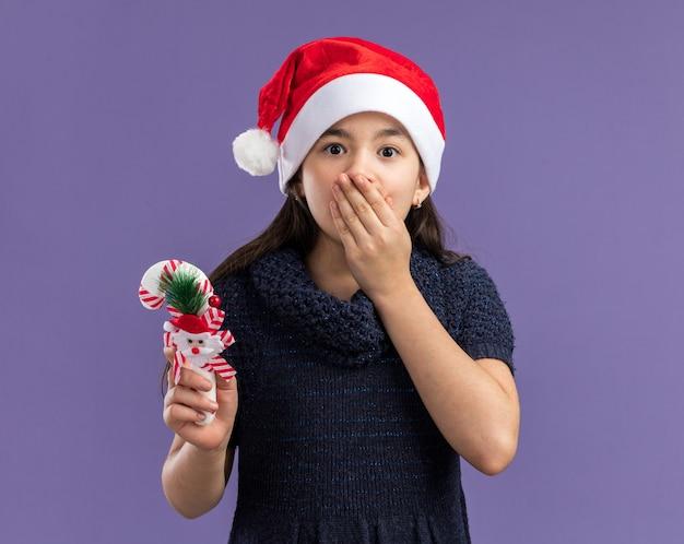 Klein meisje in gebreide jurk met een kerstmuts met kerstsnoepgoed dat geschokt is en de mond bedekt met de hand die over de paarse muur staat