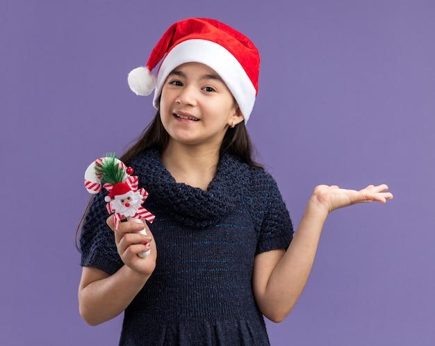 Klein meisje in gebreide jurk met een kerstmuts met kerstsnoepgoed met een glimlach op het gezicht, blij en vrolijk staande over de paarse muur