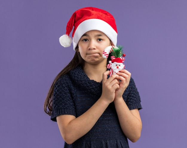 Klein meisje in gebreide jurk met een kerstmuts met kerstsnoepgoed verward met een droevige uitdrukking op het gezicht dat over de paarse muur staat