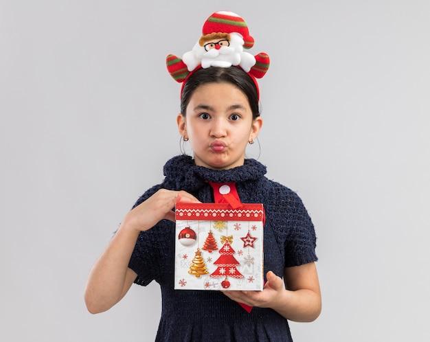 Klein meisje in gebreide jurk met rode stropdas met grappige kerst rand op hoofd bedrijf kerstcadeau op zoek verward