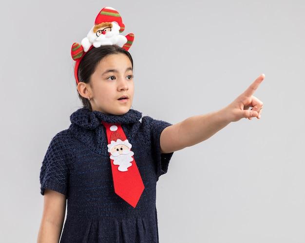 Klein meisje in gebreide jurk met rode stropdas met grappige kerstrand op hoofd wijzend met wijsvinger op iets terzijde bezorgd