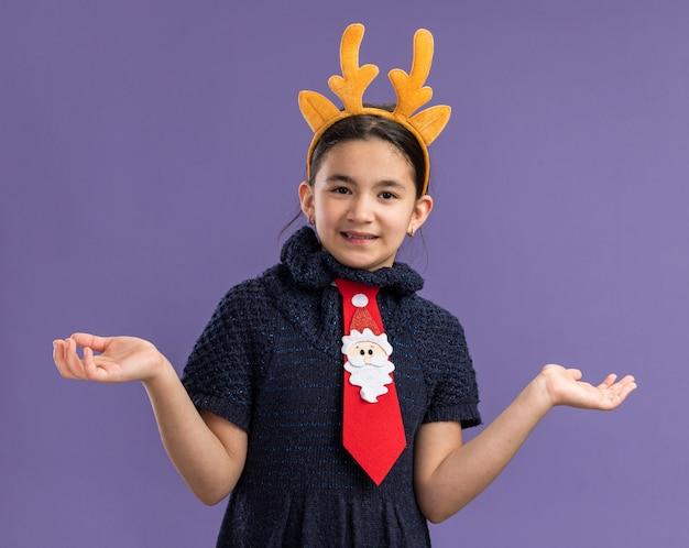 Klein meisje in gebreide jurk met rode stropdas met grappige rand met hertenhoorns op hoofd glimlachend verward spreidende armen naar de zijkanten staande over paarse muur