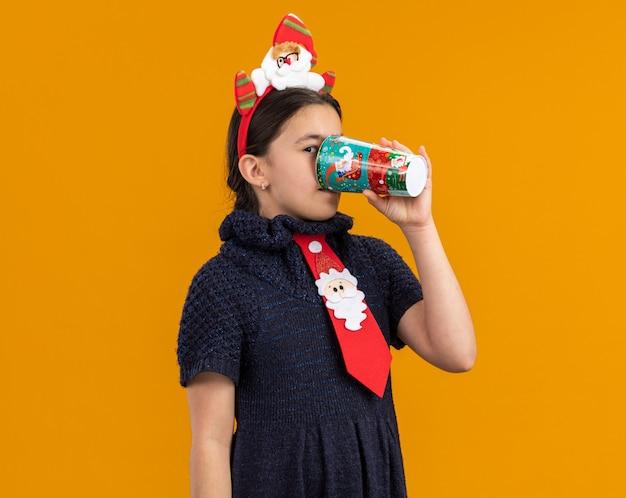 Klein meisje in gebreide jurk met rode stropdas met grappige rand op het hoofd drinken uit kleurrijke papieren beker blij en positief