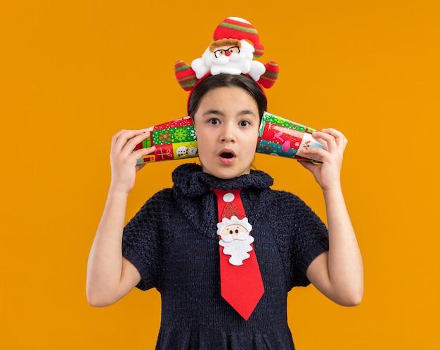 Klein meisje in gebreide jurk met rode stropdas met grappige rand op het hoofd met kleurrijke papieren bekers over haar oren en kijkt verbaasd over oranje muur