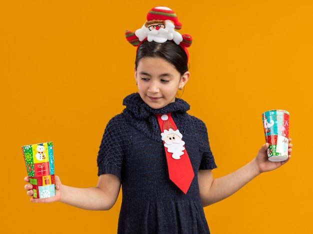Klein meisje in gebreide jurk met rode stropdas met grappige rand op het hoofd met kleurrijke papieren bekertjes kijkend verward proberen een keuze te maken staande over oranje achtergrond