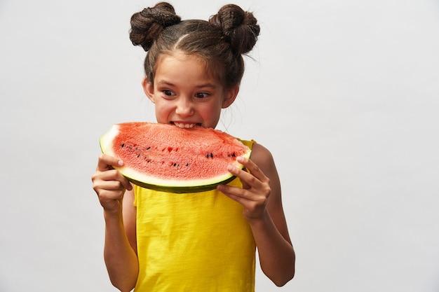 Klein meisje in geel t-shirt, lachen vrolijk en houden plakje watermeloen