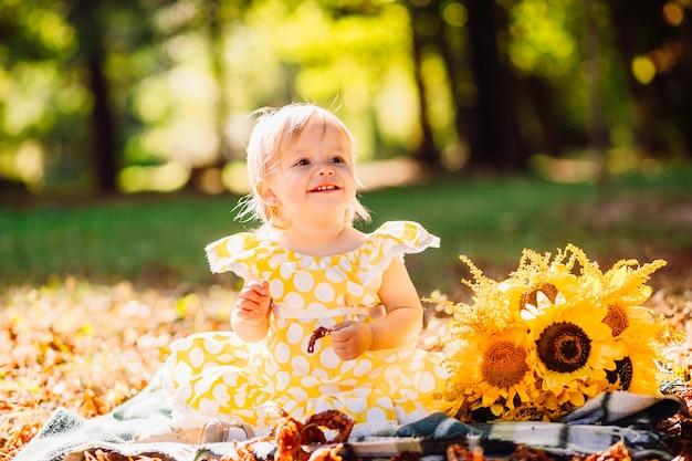 Klein meisje in gele gevlekte jurk zit op de deken in het park