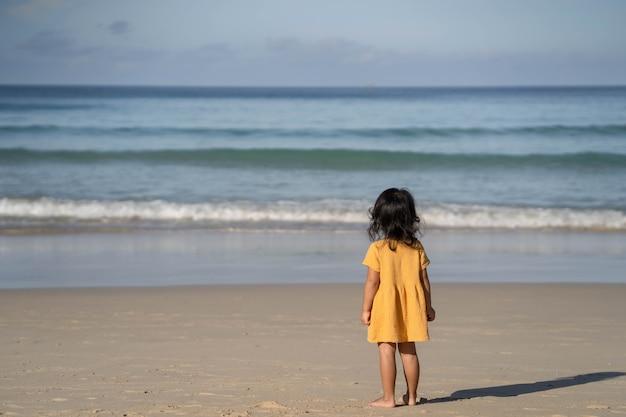 Klein meisje in gele jurk spelen op zee.