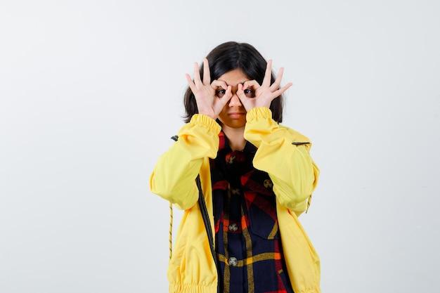 Klein meisje in geruit hemd, jas die een brilgebaar toont en er grappig uitziet, vooraanzicht.