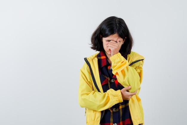 Klein meisje in geruit hemd, jas die gezicht bedekt met hand en weemoedig kijkt, vooraanzicht.