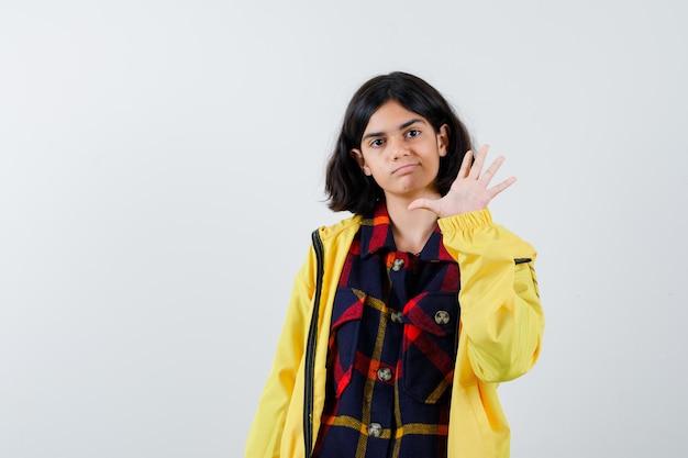 Klein meisje in geruit hemd, jas met nummer vijf en zelfverzekerd, vooraanzicht.