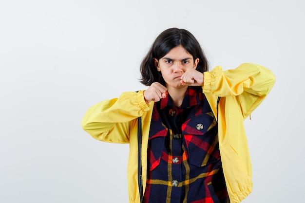 Klein meisje in geruit hemd, jas staat in vechthouding en ziet er hatelijk uit, vooraanzicht.