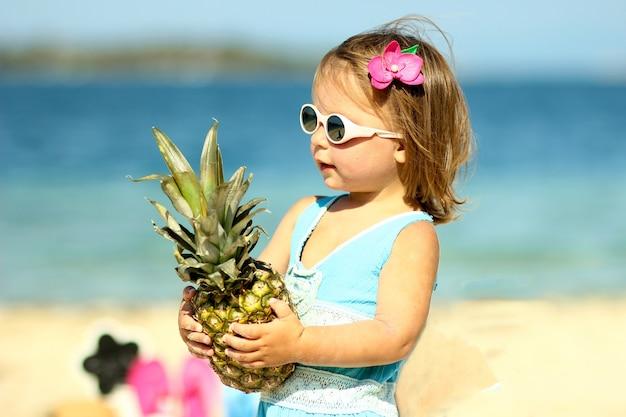 Klein meisje in glazen met ananas in de buurt van de zee zomer