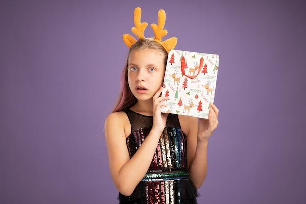 Klein meisje in glitter feestjurk en grappige hoofdband met hertenhoorns met kerstpapieren zak met geschenken kijkend naar camera geïntrigeerd en verrast over paarse achtergrond
