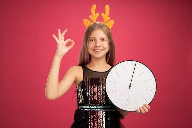 Klein meisje in glitter feestjurk en grappige hoofdband met hertenhoorns met klok glimlachend vrolijk weergegeven: ok teken nieuwjaar viering vakantieconcept permanent over roze achtergrond