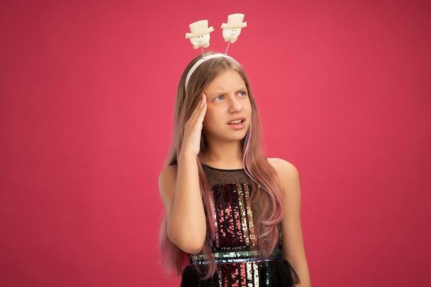Klein meisje in glitter feestjurk en grappige hoofdband opzij kijkend verbaasd, nieuwjaarsviering vakantieconcept staande over roze achtergrond