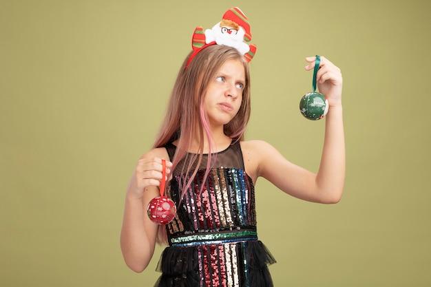 Klein meisje in glitter feestjurk en hoofdband met kerstman die kerstballen vasthoudt en er verward uitziet met twijfels die proberen een keuze te maken die over groene achtergrond staat