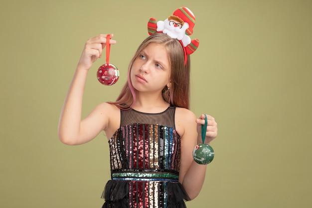 Klein meisje in glitter feestjurk en hoofdband met kerstman die kerstballen vasthoudt en verward naar hen kijkt en twijfelt over groene achtergrond