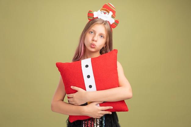 Klein meisje in glitter feestjurk en hoofdband met kerstman met grappig kussen kijkend naar camera verveeld over groene achtergrond