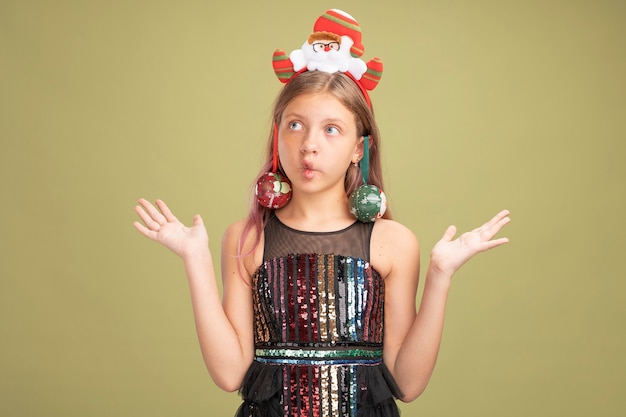 Klein meisje in glitter feestjurk en hoofdband met kerstman met kerstballen op haar oren opzij kijkend verward en onzeker over groene achtergrond