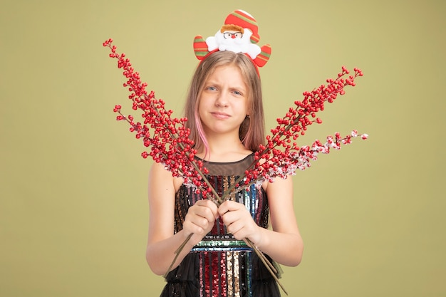 Klein meisje in glitter feestjurk en hoofdband met santa met takken met rode bessen kijkend naar camera die wrange mond maakt met teleurgestelde uitdrukking die over groene achtergrond staat