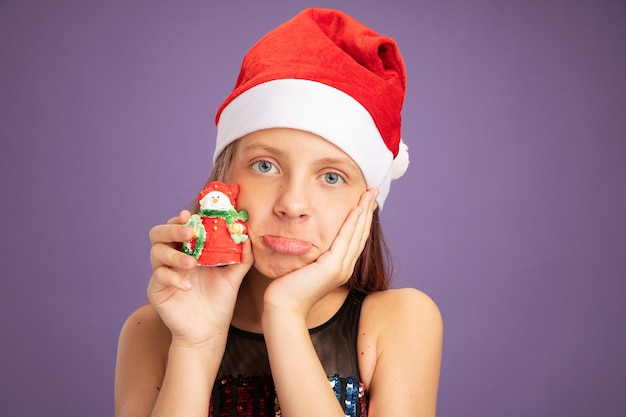 Klein meisje in glitter feestjurk en kerstmuts met kerstspeelgoed kijkend naar camera die wrange mond maakt met teleurgestelde uitdrukking die over paarse achtergrond staat
