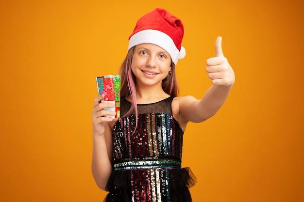 Klein meisje in glitter feestjurk en kerstmuts met twee kleurrijke papieren bekers kijkend naar camera met een glimlach op het gezicht met duimen omhoog over oranje achtergrond