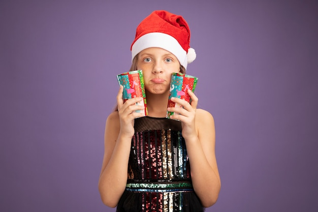 Klein meisje in glitter feestjurk en kerstmuts met twee kleurrijke papieren bekers kijkend naar camera verward over paarse achtergrond