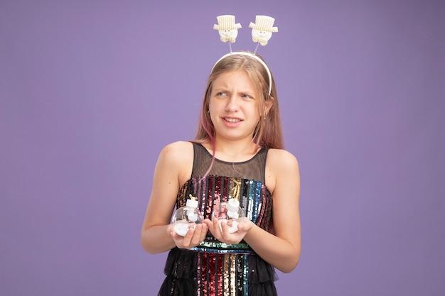 Klein meisje in glitterfeestjurk en grappige hoofdband met kerstballen die verward en ontevreden opzij kijken terwijl ze over paarse achtergrond staan