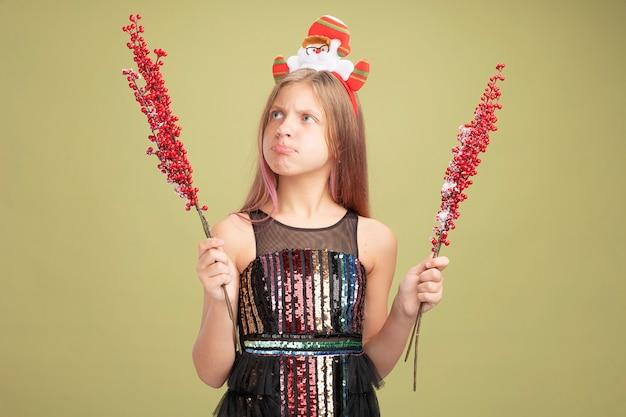 Klein meisje in glitterfeestjurk en hoofdband met kerstman die takken vasthoudt met rode bessen die er verward en onzeker uitzien over groene achtergrond