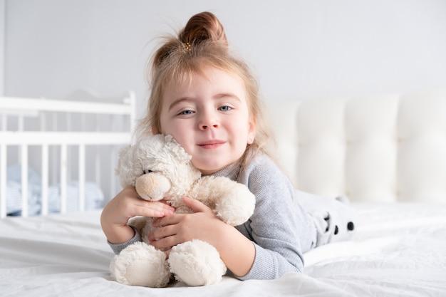 Klein meisje in grijze coltrui met teddy beer witte beddengoed glimlachen opleggen.
