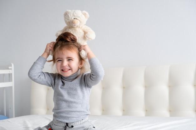 Klein meisje in grijze coltrui met teddybeer zittend op bed glimlachen.