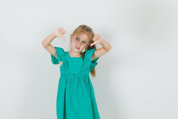 Klein meisje in groene jurk met duimen naar beneden en ontevreden op zoek