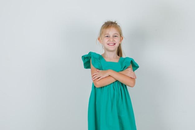 Klein meisje in groene jurk permanent met gekruiste armen en vrolijk kijken