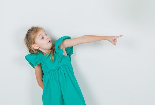 Klein meisje in groene jurk wijzende vinger naar kant en bang op zoek