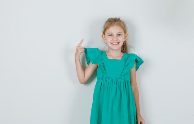 Klein meisje in groene jurk wijzende vinger weg en op zoek vrolijk